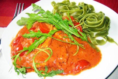 mit Tomantensoße an Rucola und grünen Bandnudeln
